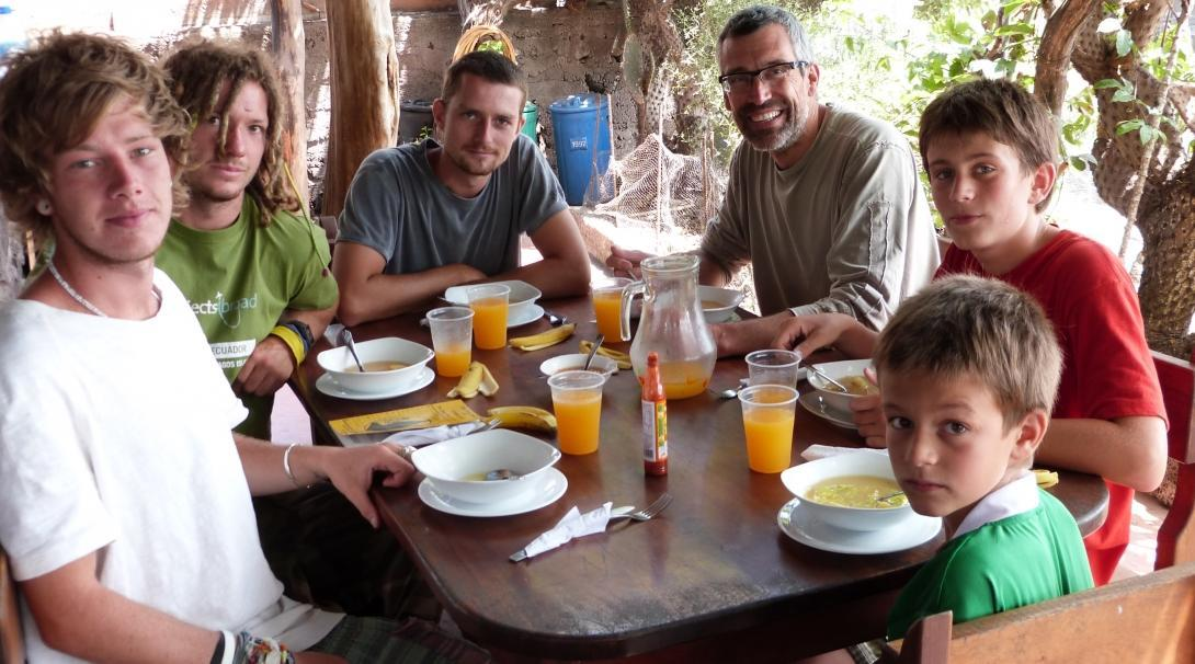 A family volunteering abroad together enjoy an afternoon meal after finishing their work for the day in the Galapagos Islands.